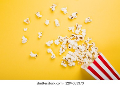 Spilled popcorn on a yellow background, cinema, movies and entertainment concept