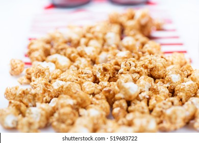 Spilled popcorn with red striped cloth and glasses for 3D movie in the background