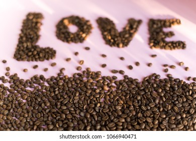 Spilled roasted coffee beans on a pink background with a love inscription.