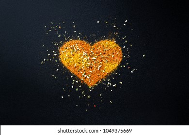 Spilled spices with love for cooking in the kitchen, the heart of the cook, a symbol of love.