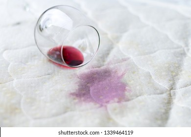 Spilled wine glass on the bed. Accidentally dropped wineglass on white bedsheet. Unlucky, unfortunate situation. Wet stain.