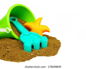 Spilling bucket of sand with beach toys on a white background