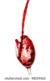 Spilling red wine in the glass on white background