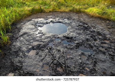 Spills of crude oil on the soil surface. Crater of the volcano.Mud volcano