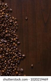 Spilt coffee beans on wood surface table.