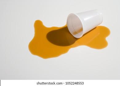 Spilt orange juice and a plastic cup