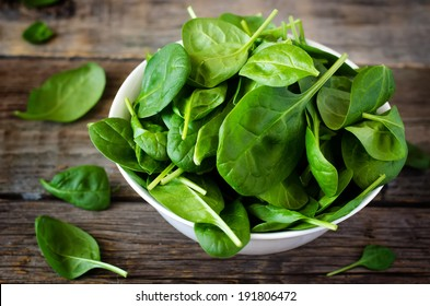 spinach in the bowl on the dark wood background. toning.