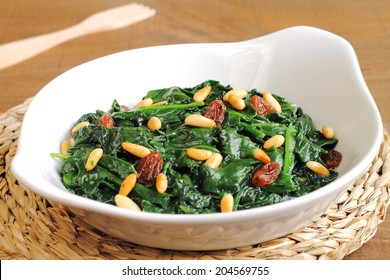 Spinach Catalan style, with raisins and pine nuts, a traditional recipe from Catalonia, Spain (Espinacas a la catalana)