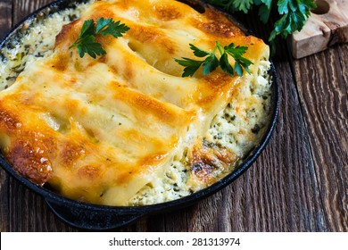 Spinach and cheese cannelloni cooked in a frying pan,  Italian cuisine