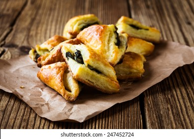 Spinach and cheese puff pastries triangles on paper