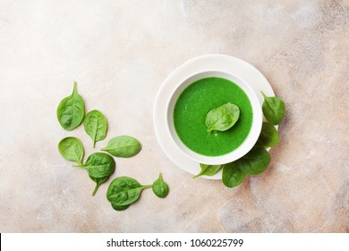 Spinach cream soup in bowl decorated spinach leaves top view.