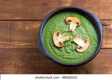 Spinach cream soup in clay bowl on wooden background. Vegetarian food. Top view