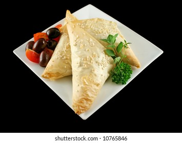 Spinach and feta cheese triangles with olives and cherry tomatoes.