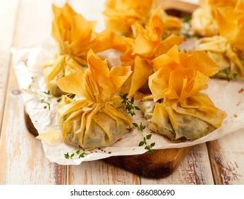 Les purées de phyllo épinards et fêta sur une table rustique en bois, délicieux amuse-gueules végétariens