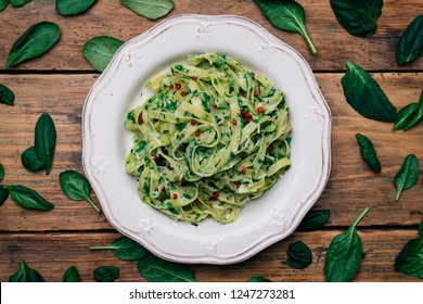 Spinach Fettuccine. Vegan pasta with spinach (Spinach Fettuccine Alfredo Pasta) on a white plate. Old wooden background