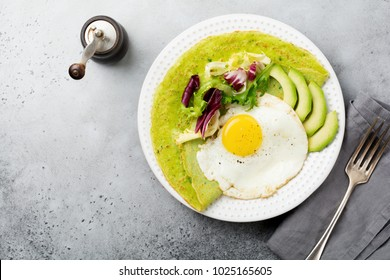 Spinach green crepes (pancakes) with fried egg, avocado and leaves of mix of salad on ceramic plate on gray concrete background. Ð¡oncept of healthy breakfast. Selective focus. Top view. Copt space.