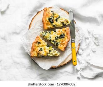 Spinach, leek, chicken, cheese pie on light background, top view