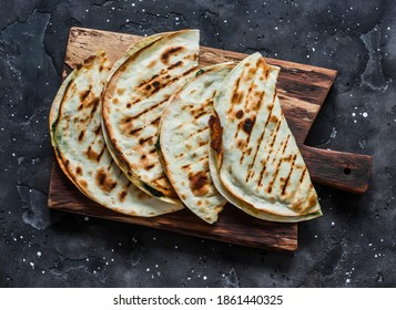 Spinach and mozzarella cheese vegetarian grilled quesadilla on a dark background, top view