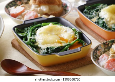 Spinach with poached egg and wooden spoon