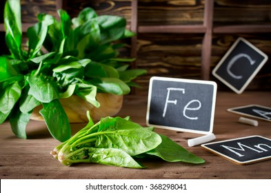 Spinach rich in vitamin C, manganese and iron on a dark background. Spinach is an annual vegetable is a herbaceous plant of the family Chenopodiaceae.