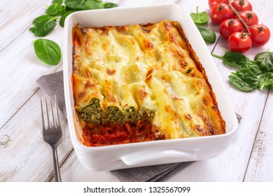 Spinach & ricotta cannelloni in a baking dish on a white background with ingredients