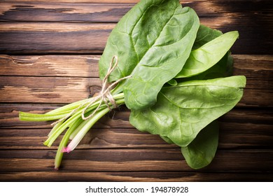 Spinach with roots on the wooden background.