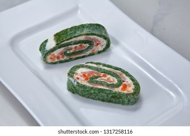 Spinach roulade filled with cream cheese, smoked salmon and trout caviar on a white plate on a light background.
