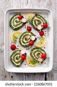 Spinach roulade stuffed with cream cheese and smoked salmon sliced on a white ceramic dish.  Delicious appetizer, party food