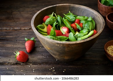 Spinach salad with avocado, strawberries and sesame seeds. Light summer salad. Healthy Eating. Closeup and dark brown wooden background