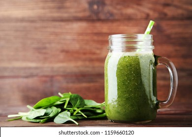 Spinach smoothie in glass jar on brown wooden table