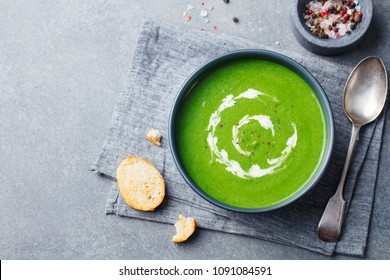 Spinach soup with cream in a bowl. Grey stone background. Copy space. Top view.