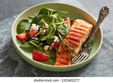 Spinach and strawberry salad with grilled salmon