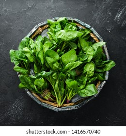 Spinach in a wooden box. Healthy food. Top view. Free space for your text.
