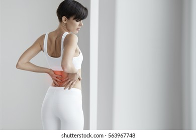 Spinal Pain. Female Suffering From Painful Feeling, Backache Or Kidney Pain, Holding Hands On Body. Beautiful Young Woman Feeling Back Pain, Having Health Issues. Health Care Concept. High Resolution