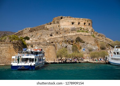 Spinalonga / Greece - September 27, 2018: Cruise to the island of Spinalonga. Small boat on the blue lagoon. Spinalonga fortress on the island of Crete, Greece. Architecture on the island.