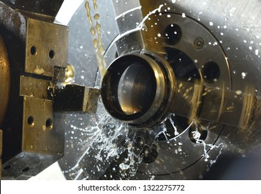 Spindle chuck and installed metal part in pocessing on high precision Cnc industrial lathe turning machine. CNC machine cuts off excess edges on metal part
