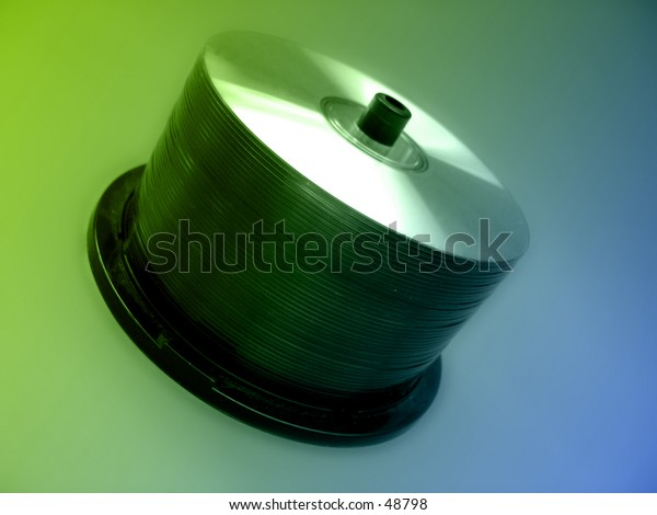 A spindle full of blank CD's on a green/blue background.