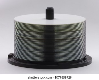 A spindle stack of blank DVDs or CDs is shown, set against a white background.