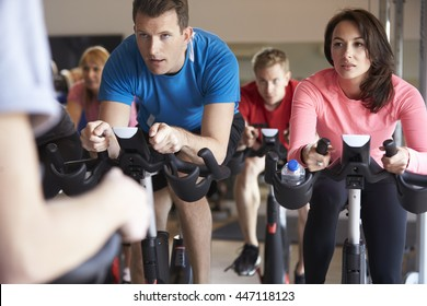 Spinning class on exercise bikes at a gym, close up