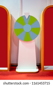 Spinning colorful fortune wheel with white stand on orange ground floor