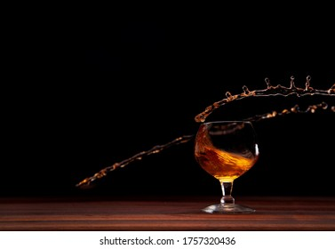 Spinning glass of brandy splashing with a black background