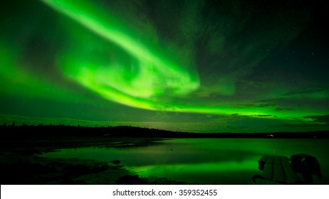 Spinning Lights - Bands of bright northern lights spinning across the starry night sky over a lake.