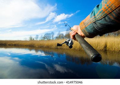 Spinning in one hand. Fisherman start to fishing on the river in sunny weather. Fish hunting process. Eye view