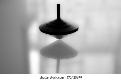 Spinning top in action on a mirror surface