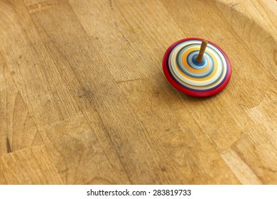 Spinning top. A wooden spinning-top in action on a wooden handmade table.
