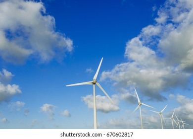 Spinning wind turbine on a cloudy day. Modern technology of electrical power generation. Renewable energy sources concept. Environmentally friendly energy production. Close up