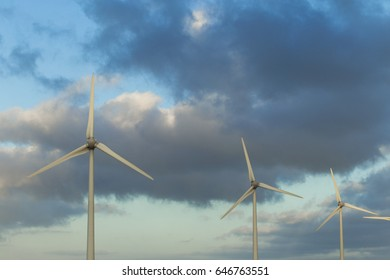 Spinning wind turbines on a cloudy day. Modern technology of electricity generation. Renewable energy sources concept. Environment friendly electricity production. Close up