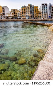 Spinola Bay water and stony bottom in the foreground, St. Julian's architecture in the background, at St. Julian's Malta