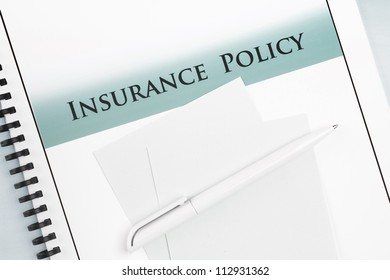 Spiral back Insurance Policy document with pen and notepaper.