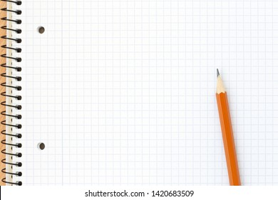 Spiral blank notebook in the cell with pencil. Close up, top view. School concept.